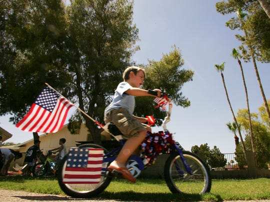 """Tommy Billings races his star-spangled bike after decorating it for the upcoming """"Red, White and Boom"""" Independence Day celebration in Ahwatukee."""