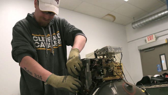 Chris Mitchell takes apart the components that make up a computer monitor at NewHope Industries. Tearing down the monitor is part of the eRecycling program.