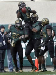 Michigan State safety Isaiah Lewis (9) is lifted by