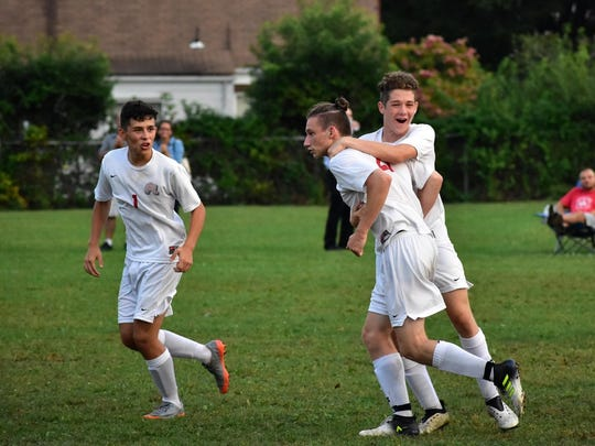 Evan Gould (21) is embraced by a teammate during Fair