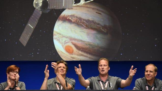 NASA scientists celebrate Juno's successful placement into Jupiter's orbit.