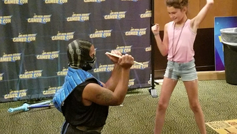 Dangerous Dan, a 4th degree black belt in Tae Kwon Do, helps a kid break a board at New Jersey Gamer Con at the Crowne Plaza Philadelphia-Cherry Hill on Sunday, July 8.