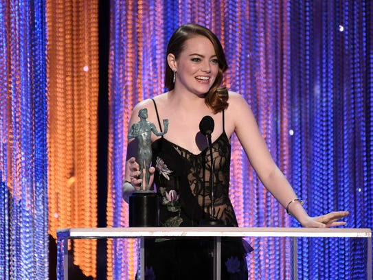 Emma Stone accepts the award for lead actress in a