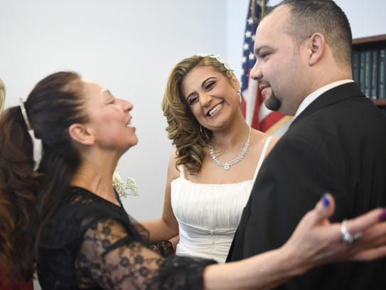 Lucia Hernandez, left, congratulates newly weds Mary
