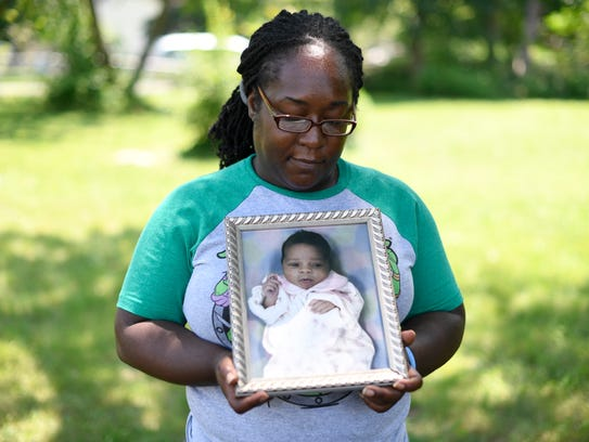 Tinisha Hood holds a portrait of her daughter Miqhayla