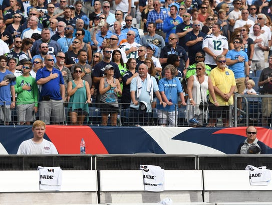 The Seahawks' bench is empty as fans stand during the