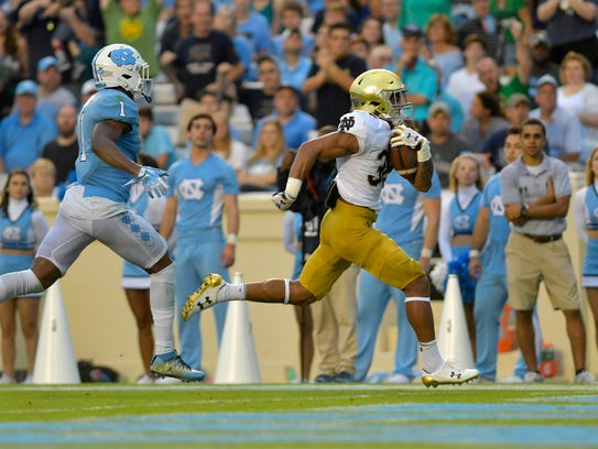 Notre Dame running back Deon McIntosh (38) runs for