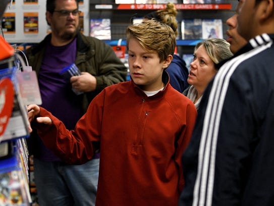 Bryson Rinker, 12, shopping in GameStop with his mother
