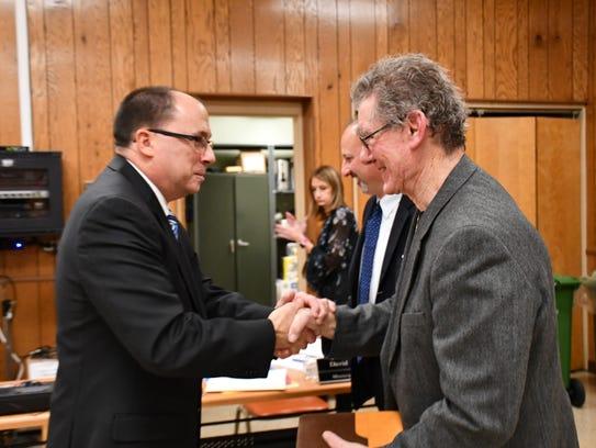 New South Hackensack Mayor Gary Brugger shakes hands