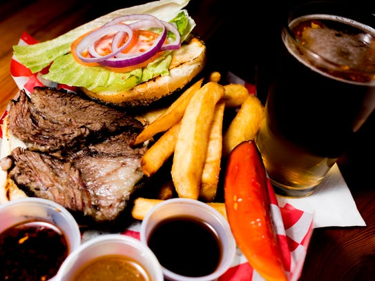 Troubadour Roadhouse and Performance Hall's signature dish, the brisket sandwich, comes with pub style fries, a pucker pickle and spicy, savory and sweet sauces, and a Miller Lite, as featured here. The restaurant at 4705 Old Kingston Pike features a full bar, dining hall and a performance stage for music and live acts.