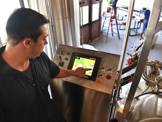 Matt Bitsche operates the controls on the brewing