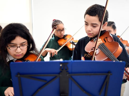 Hector Otero, right, 12, practices the viola in class