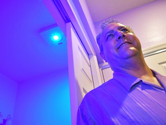 Mark Nathan, president & CEO of Violet Defense Technology standing next to a bathroom bathed in violet light where they have installed one of their products. The light will automatically turn off if anyone enters the room.