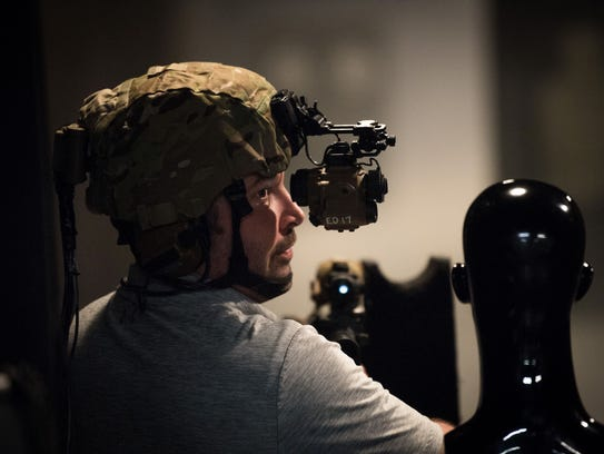 Mike Moore, a range manager at Fort Belvoir, Va., demonstrates the latest night vision goggles in a special indoor range where soldiers can use a smoke machine to obscure targets.