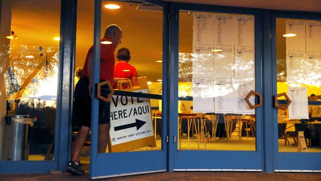 Poll marshal Steve Coulter pulls signs at the polling site at Ascension Lutheran Church after polls closed Aug. 30, 2016, in Paradise Valley.
