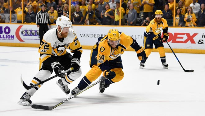 Predators defenseman Roman Josi, right, battles for the puck with Penguins right wing Patric Hornqvist, left, during the first period of Game 6 of the Stanley Cup Final at Bridgestone Arena in Nashville.