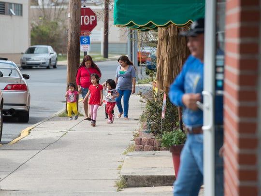 Women walk children along N. Race Street in Georgetown.