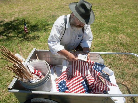 Steve Schleder gets American flags ready to place on marked and unmarked graves at Cemetery Memorial Park in preparation for Memorial Day.
