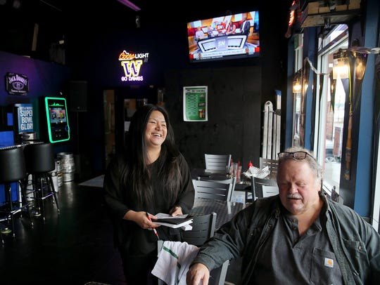 Amy Creed laughs with customer Donn Hughes in the bar of Amy's on the Bay restaurant in Port Orchard in 2017. The iconic restaurant on Bay Street closed Dec. 31 after no buyers stepped forward. Creed took another job with a more regular schedule.