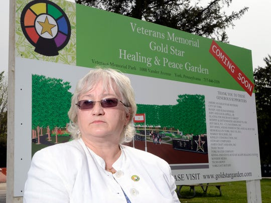 In this file photo, Gold Star mother Cher Kondor stands in front of the sign for the Veterans Memorial Gold Star Healing & Peace Garden, Monday May 2, 2011.  John A. Pavoncello photo
