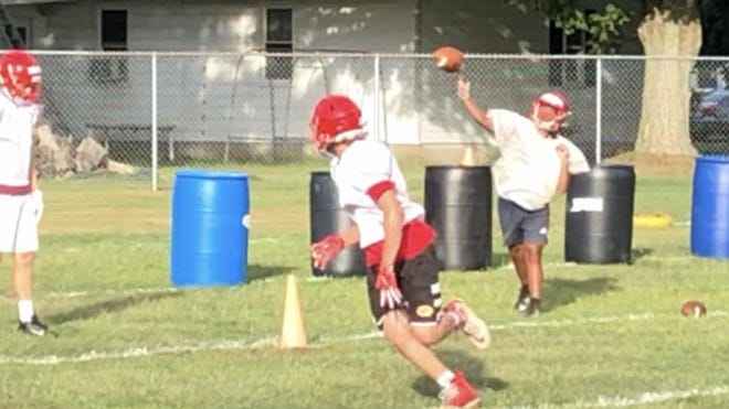 Girard football players run a passing drill last week.