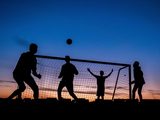In this July 10, 2018 photo four boys play soccer after