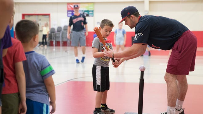 Chillicothe Paints infielder Drew DeVine shows Miles Gray how to stand and hit a ball as children from the Ross County YMCA Summer Day Camp play t-ball with some of the Chillicothe Paints players.