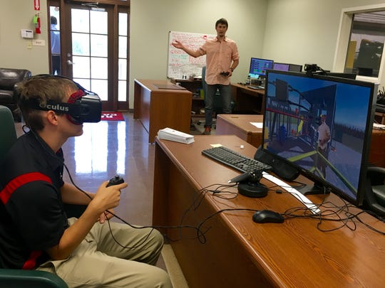 University of Louisiana of Lafayette students Matt Prilliman (front) and Kary Ritter (back) demonstrate a new virtual reality application they created that allows users to take an interactive tour of the Cleco Alternative Energy facility in Crowley and learn about engineering in the process. Ritter can be seen pointing in the background and on the computer screen.