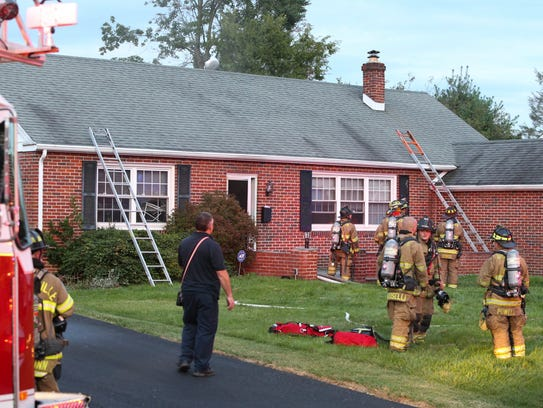 Firefighters work after extinguishing a blaze in a