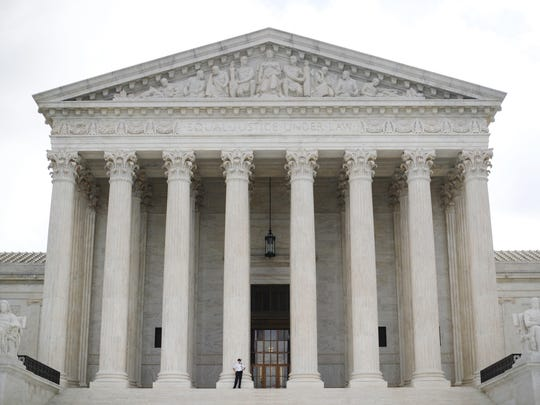 In this Oct. 9, 2018 photo, police office guards the main entrance to the Supreme Court in Washington.