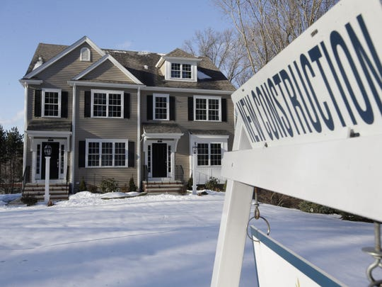 In this Thursday, Feb. 21, 2019 photo a sign is posted near a newly constructed home in Natick, Mass. On Thursday, March 14, the Commerce Department reports on sales of new homes in January.