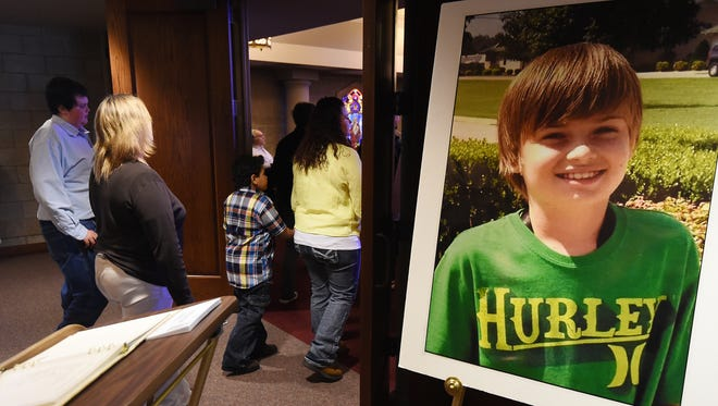 Family and friends of Austin K. Snyder pass by a photograph of the 12-year-old boy at Saturday's funeral service. Austin passed away March 2 after years of battling cancer.