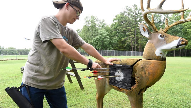 Malcolm Novak pulls arrows from a deer archery target on Wednesday. Part of the qualification for the urban hunts in Bull Shoals and Lakeview is the ability to put three arrows in the kill zone of a target from an elevated stand.