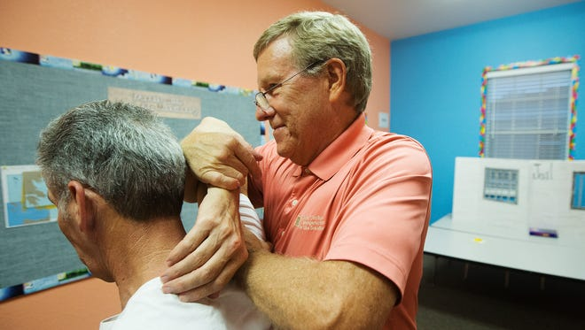 Dr. Glen Schaffer makes spinal and shoulder adjustments on a patient Tuesday at the Southwest Florida Free Pain Clinic at the Fort Myers First Church of The Nazarene.