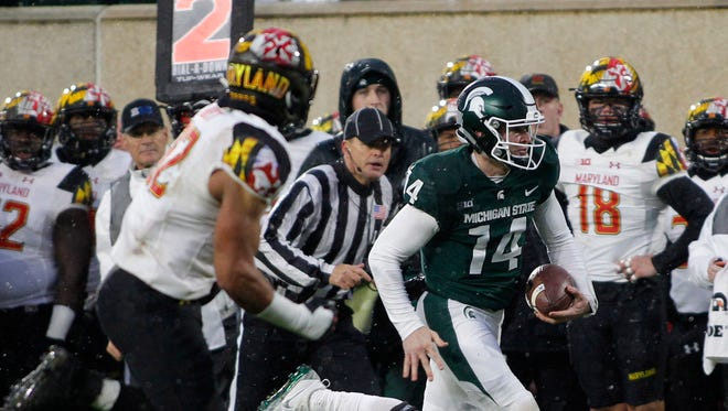 Michigan State quarterback Brian Lewerke, right, runs for a first down against Maryland's Chandler Burkett during the first half.