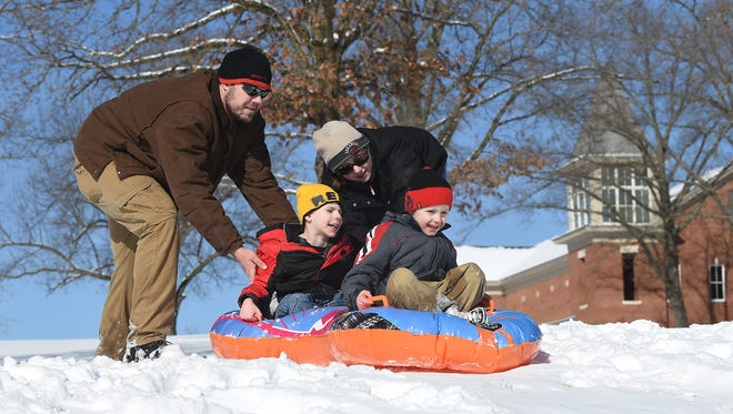 Tim and Lisa Nichols give their sons, Bryon, 8, and Raymond, 5, a push while sledding Thursday morning at Arkansas State University Mountain Home. Area students got another day off school due to Winter Storm Thor.
