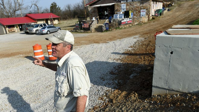 Paul Price stands at an area near Woodman's Liquor and Heidi's Ugly Cakes and Sandwiches on Fisherman Street in Norfork where he says a planned state project will create a safety hazard for customers and the public.