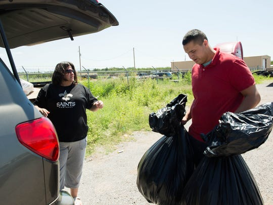Richard Bolanos, owner of Rockin Rods a custom garage, takes bags of donations of children's items clothing and shoes from Erin Carabajal, Wednesday Aug.  30, 2017 at Rockin Rods, before Bolanos leaves for Houston in a lifted truck and donated supplies for the area in Texas affected by tropical storm Harvey.