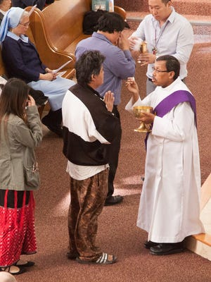 Eugenio Ramirez-Murphy, a deacon, distributes communion at Sunday Mass at St. Michael's church, 1445 N 24th St, Milwaukee. Once a German stronghold, St. Michael's Church is heavily Southeast Asian today.