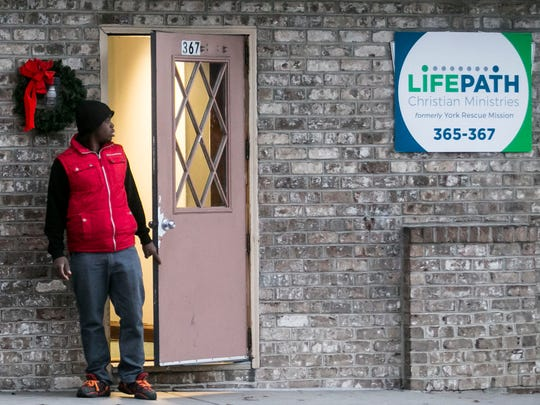 Volunteer Brandon McIntosh, of Gettysburg, walks out of LifePath Christian Ministries Thursday, Dec. 1, 2016, in York City.