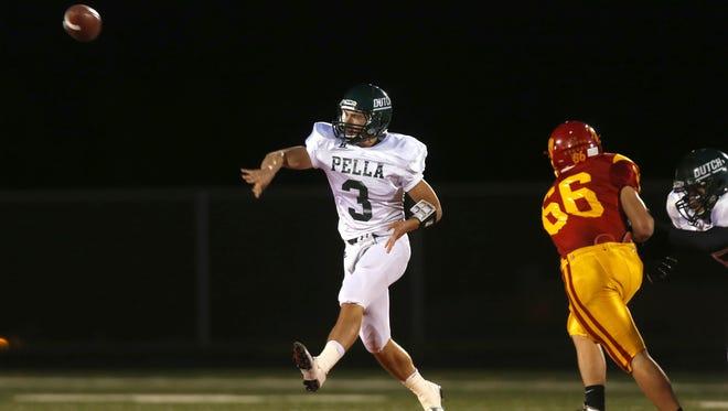 Pella quarterback Noah Clayberg throws a pass as Carlisle's Tyler Danitz (66) closes in at Carlisle High School Friday, October 3, 2014.