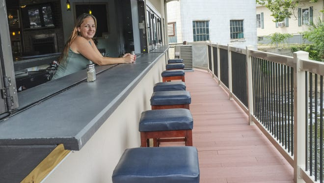 General manager of the Eaton Rapids Craft Co. restaurant in Eaton Rapids Jenny Booth, shows the outside bar area where patrons can dine over the river on Monday.