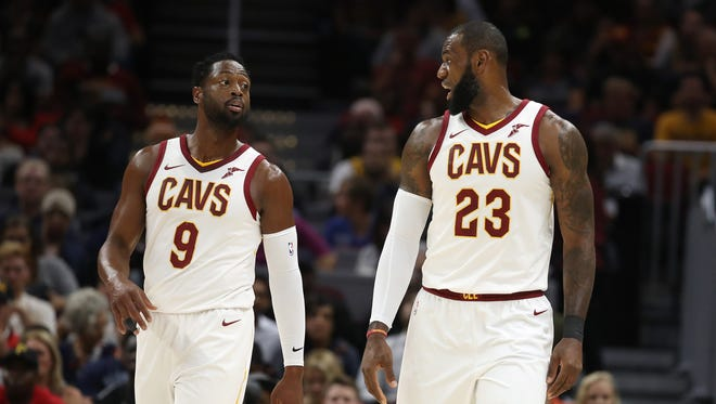 Dwyane Wade of the Cleveland Cavaliers talks with LeBron James while playing the Chicago Bulls during a pre season game at Quicken Loans Arena.