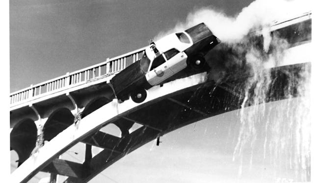 """A movie still from the 1977 film Speedtrap captures the moment a """"police car"""" is sent flying through the concrete balustrade, and off the abandoned 1913 Ash Street Bridge."""