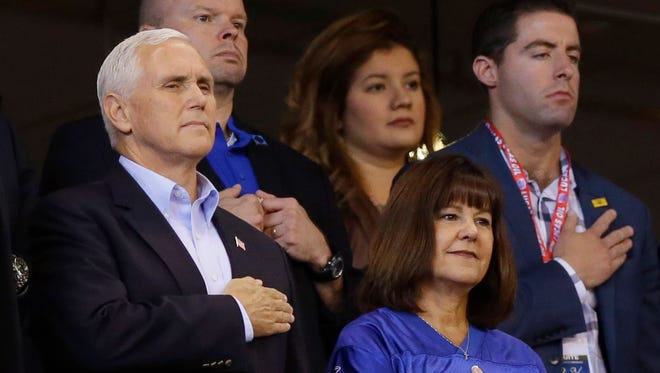 Vice President Mike Pence and his wife, Karen Pence, stand at attention during the playing of the national anthem at the Indianapolis Colts game against the San Francisco 49ers on Oct. 8, 2017. The Pences walked out a short while later to protest kneeling by some players.