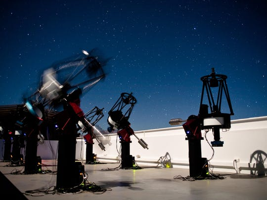 The MEarth-South telescope array, located on Cerro Tololo in Chile, searches for planets by monitoring the brightness of nearby, small stars. Use of these telescopes was critical to Dr. Jason Pittmann's discovery of a rocky planet 40 light years from Earth believed to be capable of sustaining life. This long-exposure photograph shows MEarth-South telescopes observing at night; the blurred telescope is slewing from one star to another.