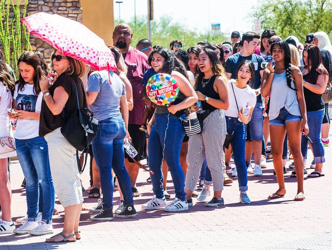 Fans wait in line to see singers Nick Jonas and Demi