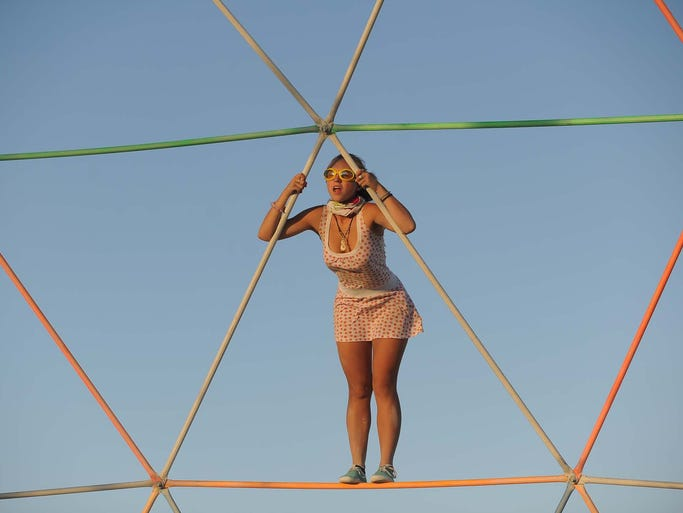 An unidentified woman climbs around on a strcture at the Burning Man Festival in Gerlach, Nev., on Sept. 1, 2009.