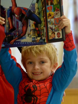 Carter Pate holds up a Spiderman book while dressed as the super hero during South Elementary's Read Across America Character Parade, Wednesday.