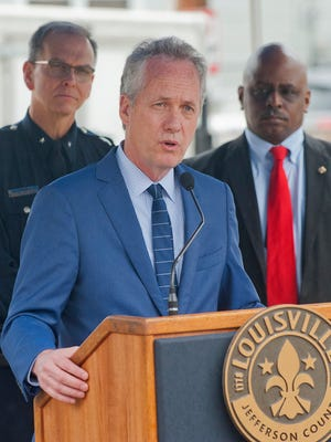 Louisville Mayor Greg Fischer speaks in March 2018, with LMPD Chief Steve Conrad (left) and Metro Council President David James (right) behind him.